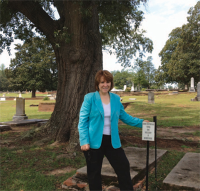 Author Victoria wilcox visits what some believe to be Doc's grave in Griffin's oak Hill Cemetery.